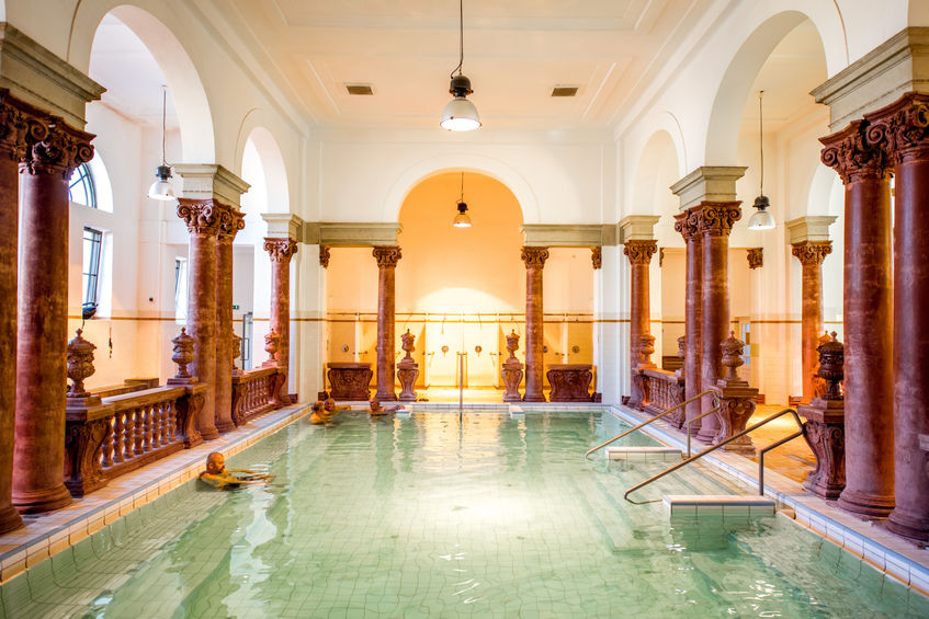 HUNGARY, BUDAPEST - MAY 21, 2018: Interior of the famous Szechenyi medicinal bath with people relaxing indoors. This place is the largest bath in Europe with thermal springs